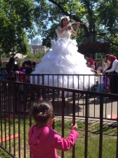 "H was enchanted by this ""princess"" on stilts who played violin. It's what kicked off her princess love."